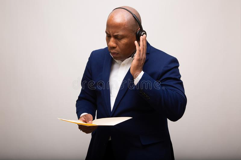 Uomo d'affari afroamericano Listens Through Headset mentre fascicolo aziendale fotografie stock libere da diritti
