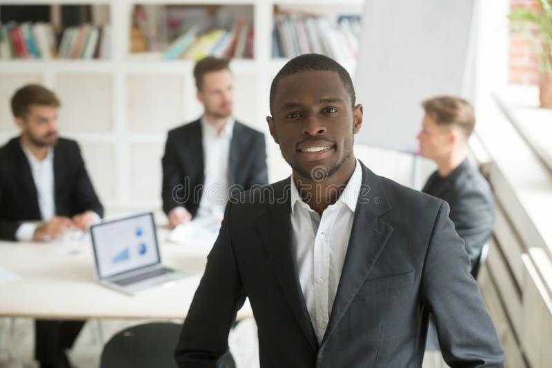 Uomo d'affari afroamericano sorridente bello che esamina macchina fotografica immagini stock libere da diritti