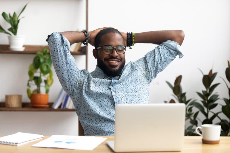 Uomo d'affari afroamericano sorridente che si tiene per mano dietro la testa che si siede all'ufficio fotografie stock