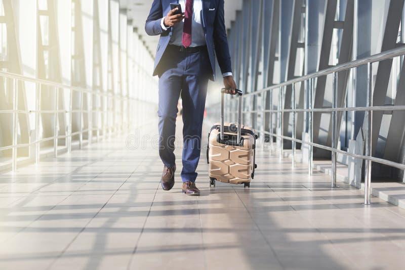 Uomo d'affari all'aeroporto che si muove verso il portone terminale per il viaggio di affari, vista frontale fotografia stock libera da diritti
