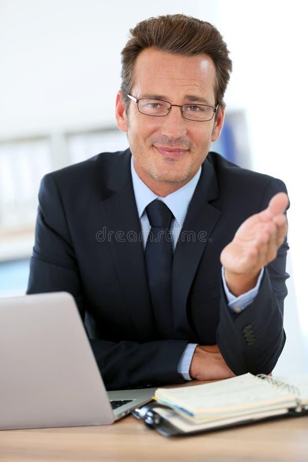Uomo d'affari all'ufficio che esprime parere al socio commerciale fotografie stock