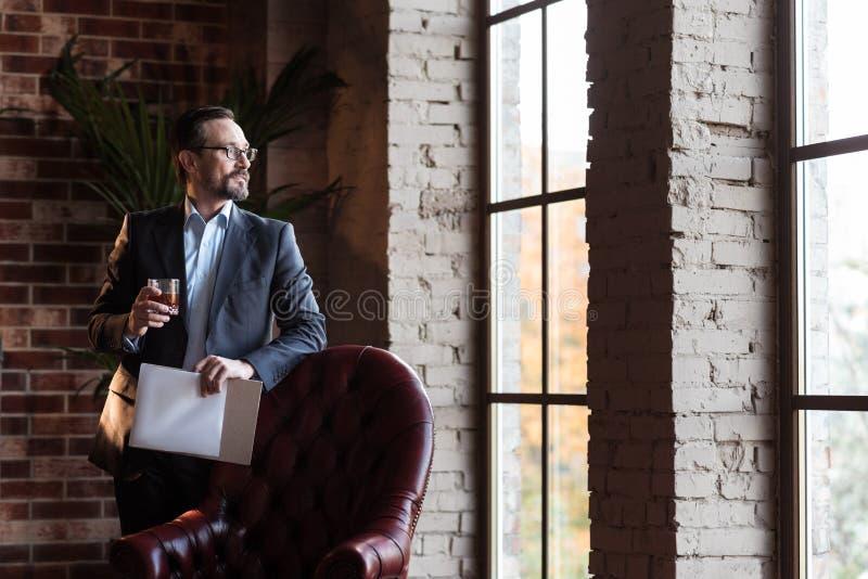 Uomo d'affari alla moda bello che esamina la finestra immagini stock libere da diritti