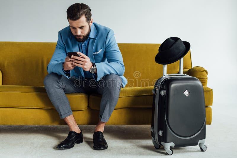 uomo d'affari alla moda bello facendo uso dello smartphone e sedersi sul sofà fotografia stock