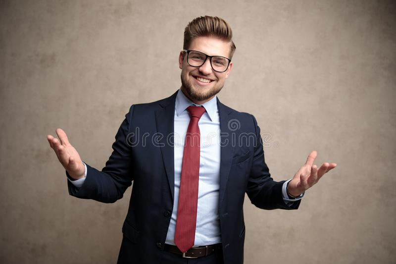 Uomo d'affari allegro che dà il benvenuto con le sue armi spalancate fotografia stock libera da diritti