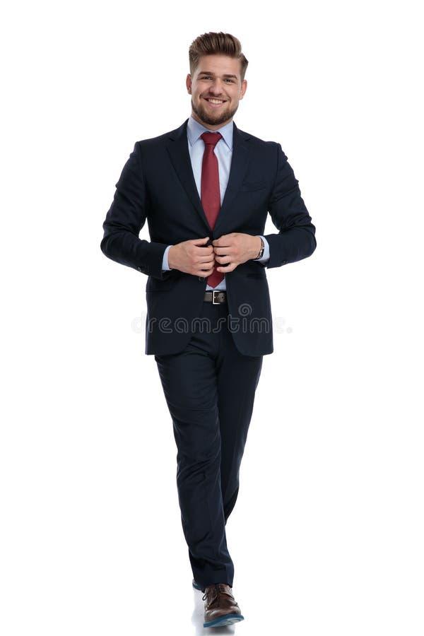 Uomo d'affari allegro che fa un passo e che regola il suo rivestimento fotografia stock