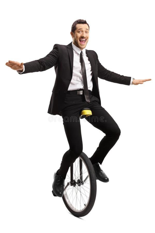 Uomo d'affari allegro che guida un monociclo che equilibra con le mani e che sorride alla macchina fotografica immagine stock
