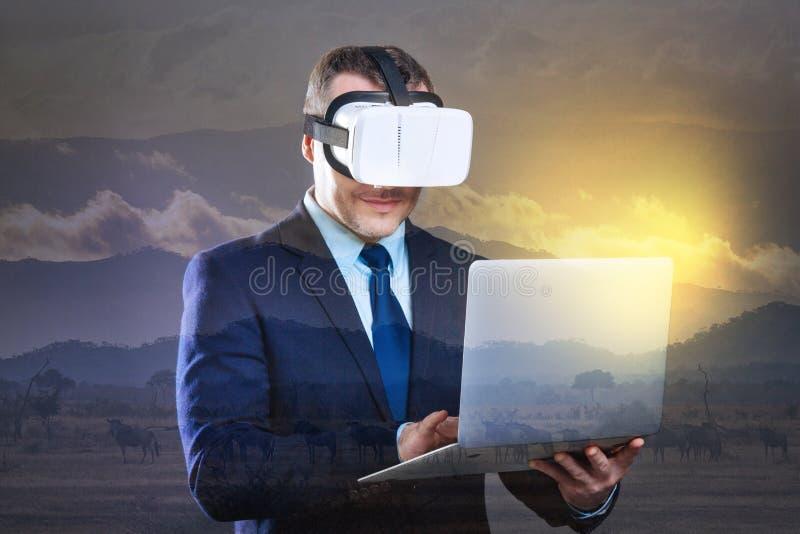Uomo d'affari allegro che lavora al computer portatile mentre indossando la cuffia avricolare di VR fotografia stock libera da diritti