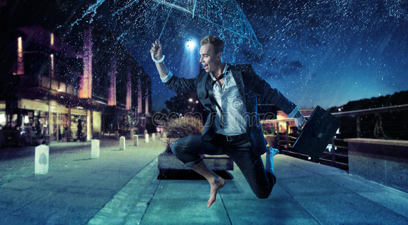 Uomo d'affari allegro che salta con un ombrello fotografie stock libere da diritti