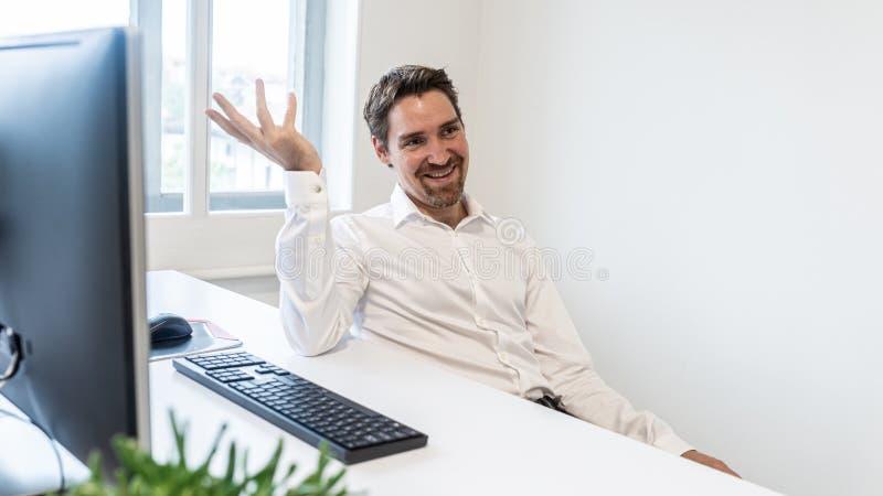 Uomo d'affari allegro che si siede alla sua scrivania fotografia stock