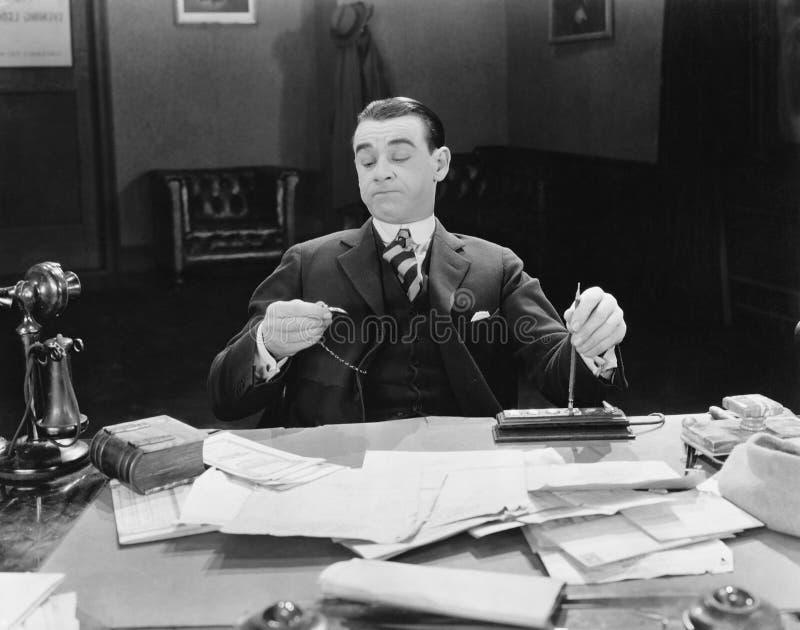 Uomo d'affari allo scrittorio che esamina orologio (tutte le persone rappresentate non sono vivente più lungo e nessuna proprietà illustrazione vettoriale