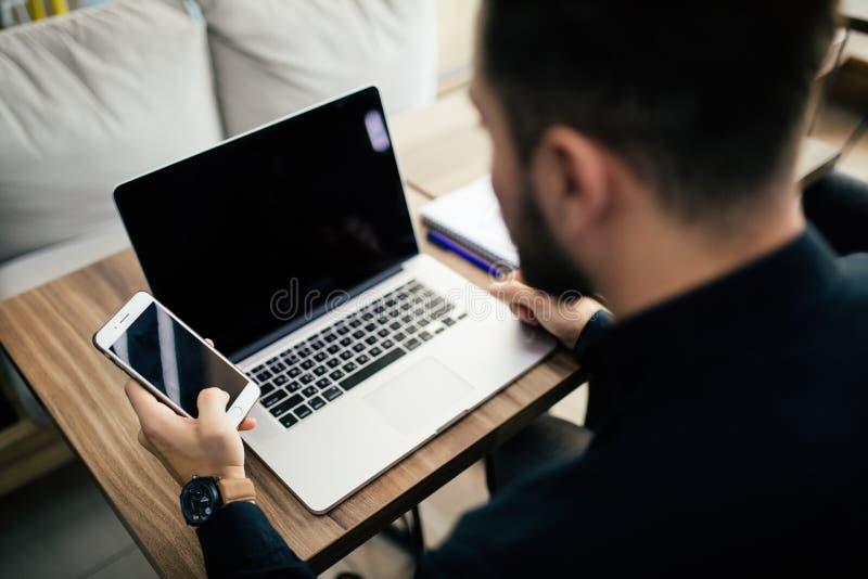 Uomo d'affari allo scrittorio con il computer portatile facendo uso di un app finanziario sul suo Smart Phone e del lavorare ai r fotografia stock libera da diritti