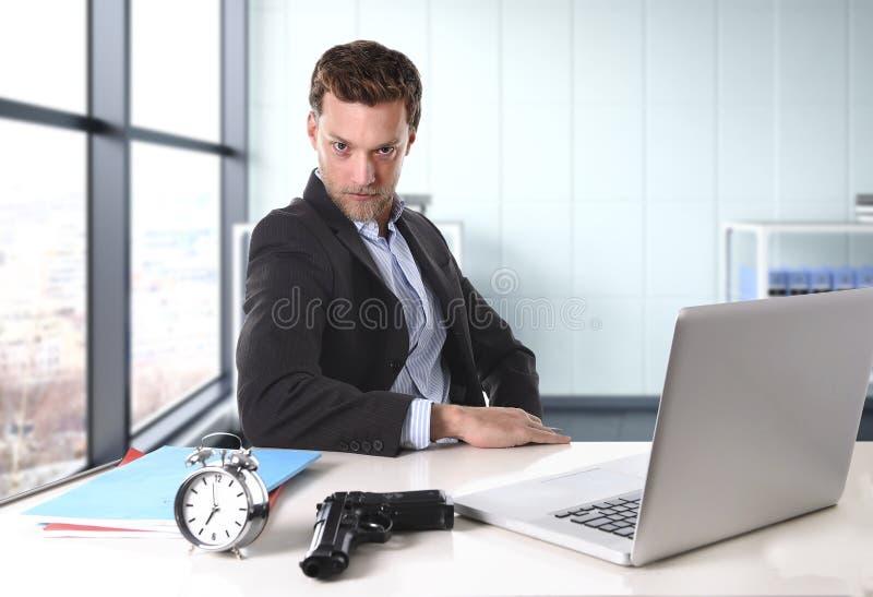 Uomo d'affari allo scrittorio del computer di ufficio che posa con la pistola e la sveglia nel concetto di termine immagine stock libera da diritti
