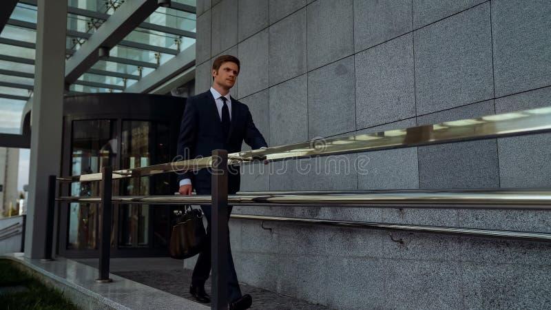 Uomo d'affari ambizioso che lascia il centro dell'ufficio dopo la riuscita riunione, routine fotografie stock