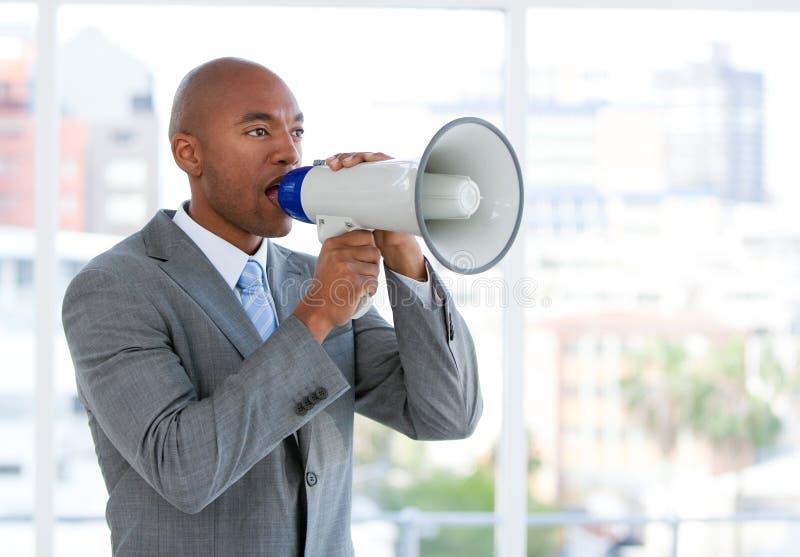 Uomo d'affari ambizioso che urla tramite un megafono fotografia stock