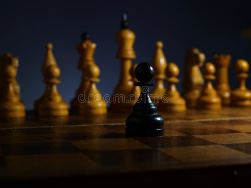 Uomo d'affari ambizioso coraggioso e sfida Pegno di legno nero e scacchi fotografie stock