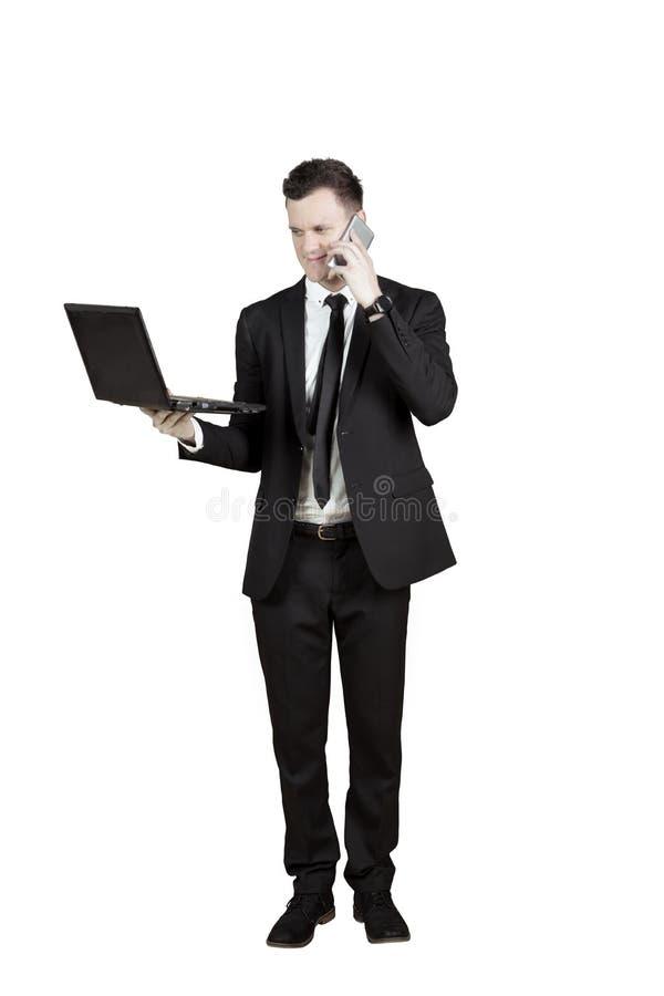 Uomo d'affari americano con lo smartphone ed il computer portatile fotografia stock