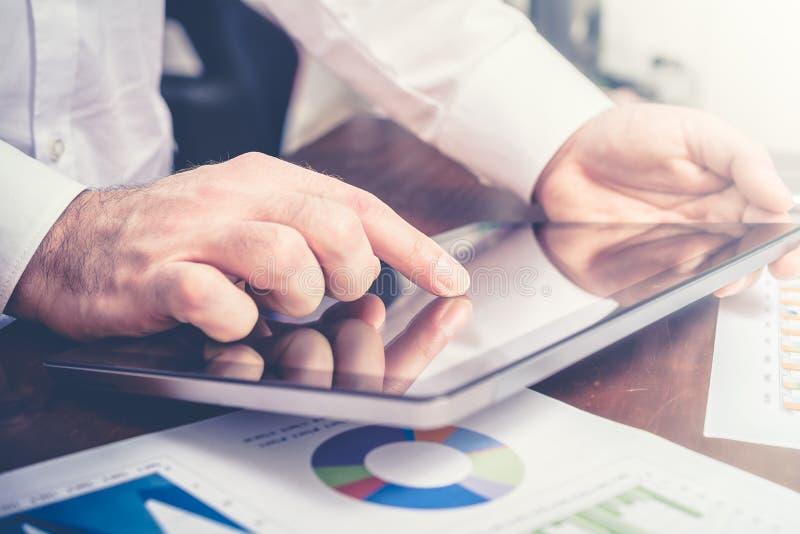 Uomo d'affari Analyzing Financial Statistics con la compressa immagini stock libere da diritti