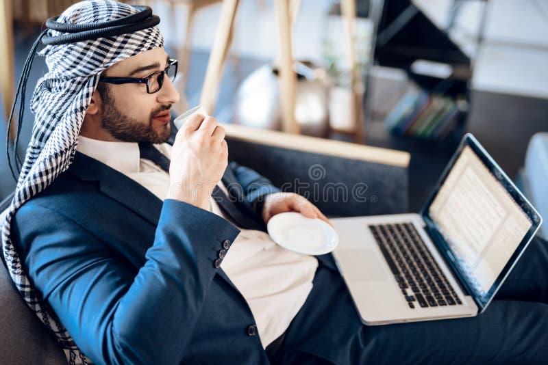 Uomo d'affari arabo rilassato su lapton con caffè sullo strato a camera di albergo fotografie stock libere da diritti