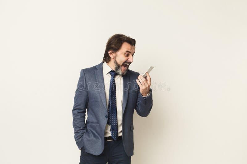 Uomo d'affari arrabbiato che grida sul telefono al fondo bianco immagine stock libera da diritti
