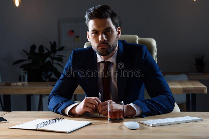 uomo d'affari arrabbiato che si siede alla tavola con vetro di whiskey e di sguardo fotografia stock libera da diritti
