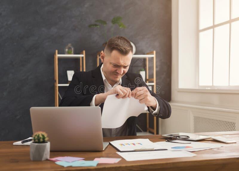 Uomo d'affari arrabbiato che strappa su un documento fotografie stock libere da diritti