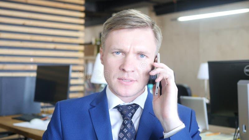 Uomo d'affari arrabbiato di Seroius giovane che parla su uno smartphone immagini stock libere da diritti