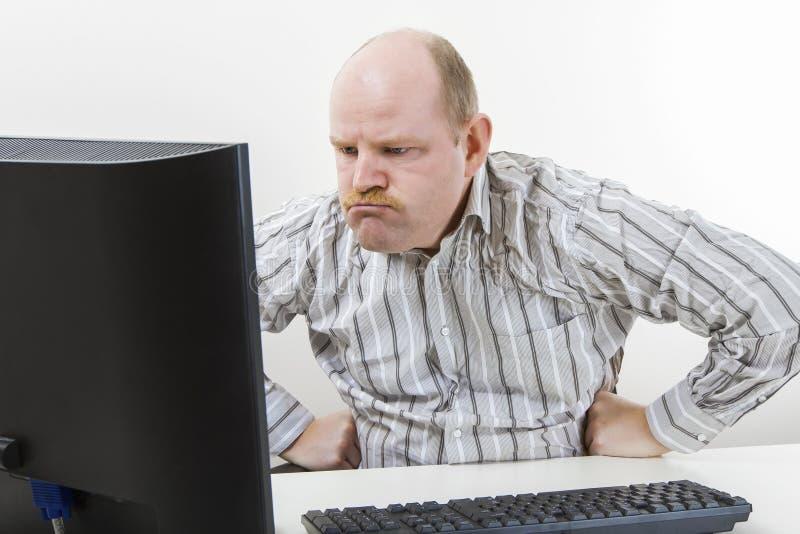Uomo d'affari arrabbiato Looking At Computer in ufficio fotografia stock libera da diritti