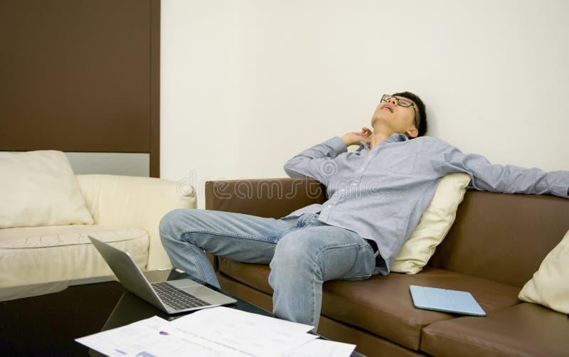 Uomo d'affari asiatico che dorme sul sofà in salone alla notte immagine stock