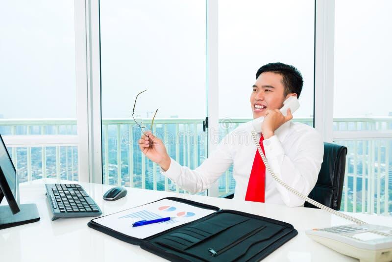 Uomo d'affari asiatico che lavora nell'ufficio immagine stock