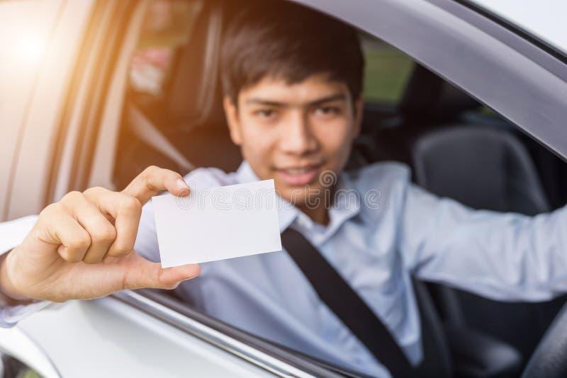 Uomo d'affari asiatico che si siede nell'automobile moderna e che tiene spazio in bianco di fotografia stock