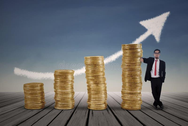 Uomo d'affari asiatico che sta accanto al grafico delle monete di oro immagini stock libere da diritti