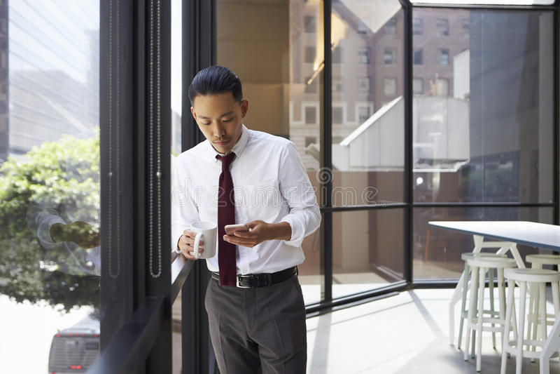 Uomo d'affari asiatico che sta nell'ufficio moderno facendo uso del telefono immagine stock