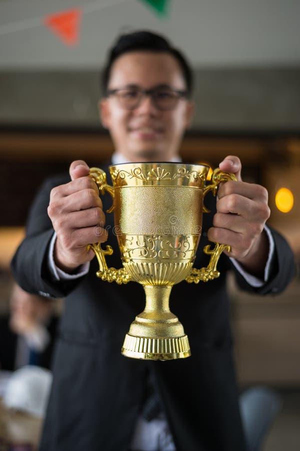 Uomo d'affari asiatico che tiene una tazza dorata del trofeo ad allegro e celebrata il suo riuscito nella carriera e nella missio fotografie stock libere da diritti