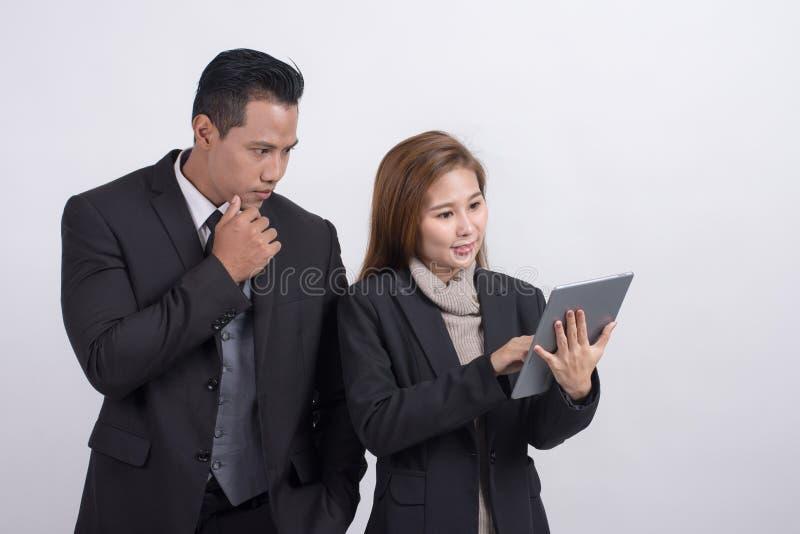 Uomo d'affari asiatico e donna di affari che discutono le idee e che per mezzo della compressa digitale su un fondo bianco fotografie stock