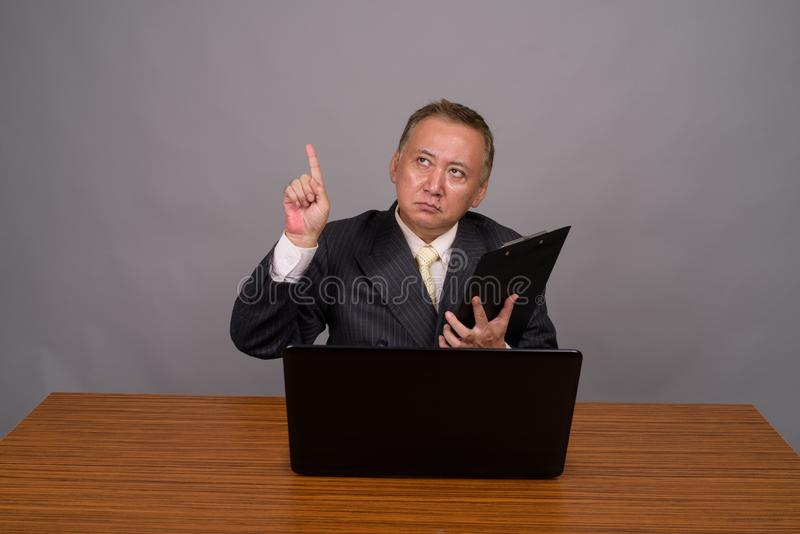 Uomo d'affari asiatico maturo che si siede con la tavola di legno contro grigio fotografia stock
