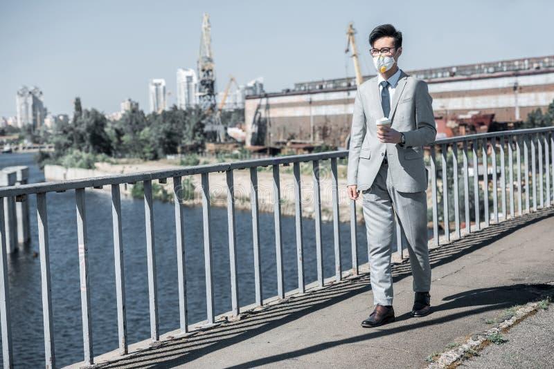 uomo d'affari asiatico nella maschera protettiva che cammina sul ponte con caffè per andare ventilare immagini stock libere da diritti