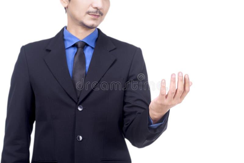 Uomo d'affari asiatico sorridente nella condizione del vestito con la palma aperta per la tenuta o la mostra del qualcosa immagine stock