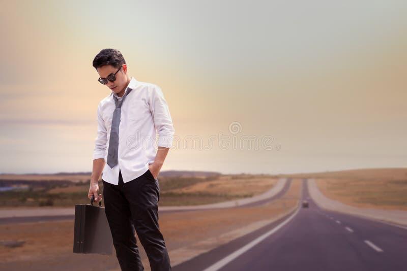 Uomo d'affari asiatico stanco e condizione sulla strada a fuori città da fotografia stock libera da diritti