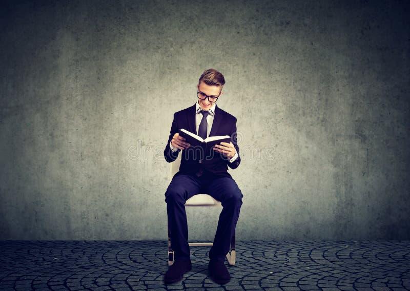 Uomo d'affari astuto che istruisce con la lettura del libro fotografia stock