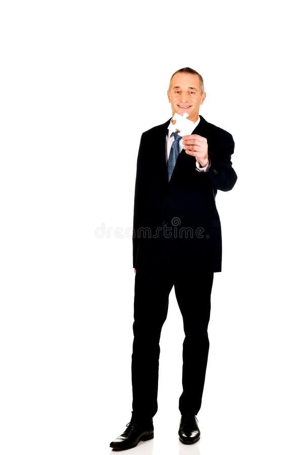 Uomo d'affari astuto che tiene un puzzle immagine stock libera da diritti