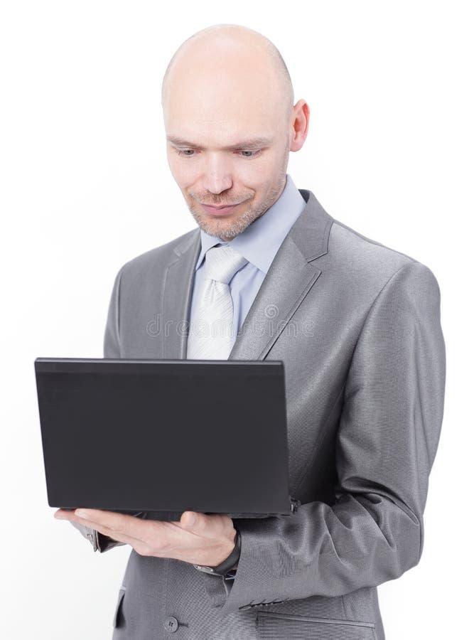Uomo d'affari attento che sta con un computer portatile Isolato su bianco immagine stock libera da diritti