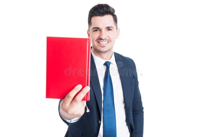 Uomo d'affari attraente allegro che dà un libro e sorridere fotografia stock libera da diritti