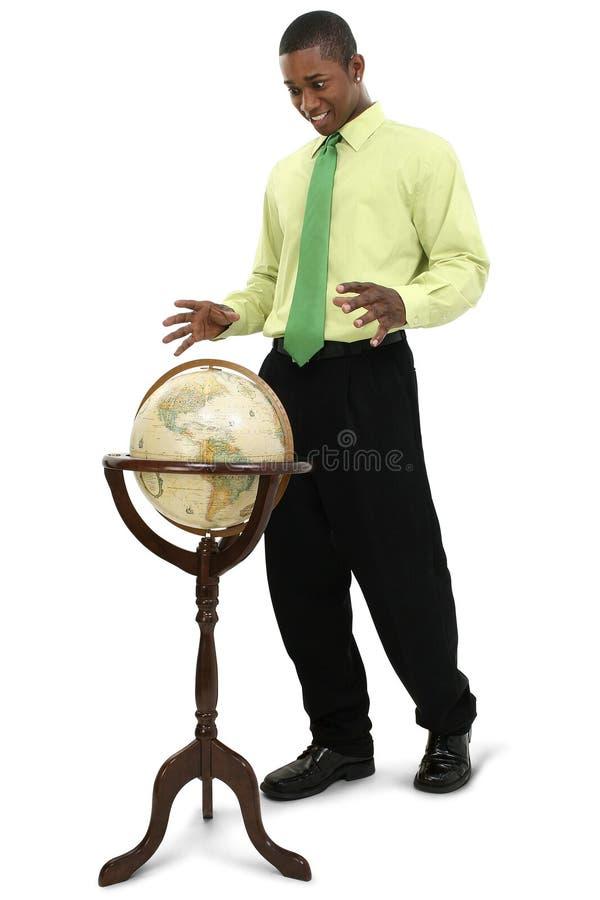 Uomo d'affari attraente che raggiunge per il globo fotografia stock