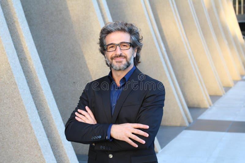 Uomo d'affari attraente con il ritratto di vetro che posa con il riuscito CEO di espressione o direttore della società immagine stock libera da diritti