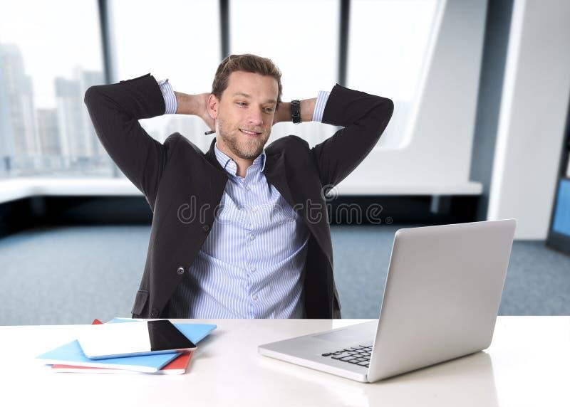 Uomo d'affari attraente felice al lavoro d'ufficio che si siedono allo scrittorio del computer soddisfatto ed a sorridere rilassa immagine stock