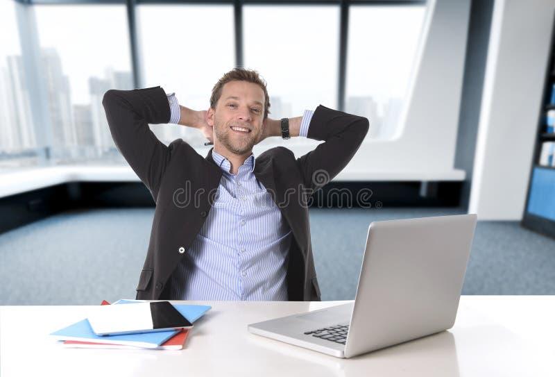 Uomo d'affari attraente felice al lavoro d'ufficio che si siedono allo scrittorio del computer soddisfatto ed a sorridere rilassa fotografia stock libera da diritti