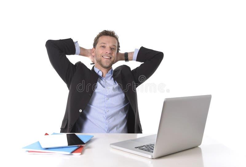 Uomo d'affari attraente felice a sorridere del lavoro rilassato allo scrittorio del computer fotografia stock