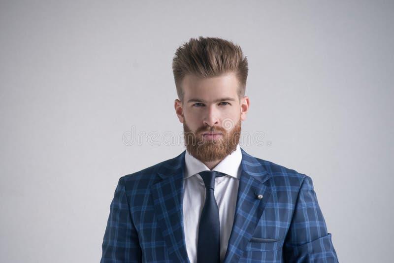 Uomo d'affari barbuto bello alla moda che esamina macchina fotografica isolata su grigio fotografie stock