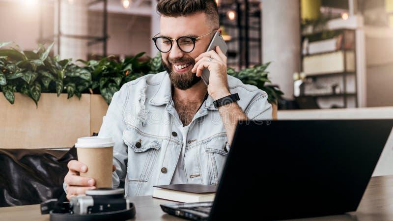 Uomo d'affari barbuto, blogger che si siede in caffè, parlando sullo Smart Phone, lavorante al computer portatile, free lance che immagine stock libera da diritti