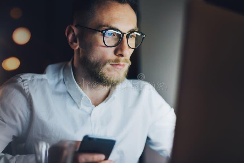 Uomo d'affari barbuto del ritratto che lavora all'ufficio moderno del sottotetto alla notte Uomo che per mezzo dello smartphone c fotografia stock libera da diritti